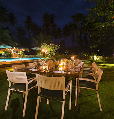 wicker dining table set by the pool at night