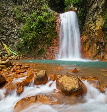 waterfalls flowing into a river with sulfur rocks