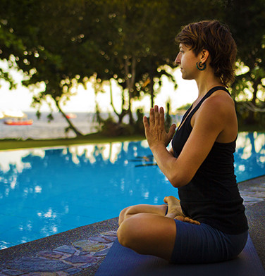 girl in black yoga outfit meditating beside the pool