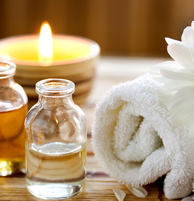 massage oils, scented candles and white towel for spa