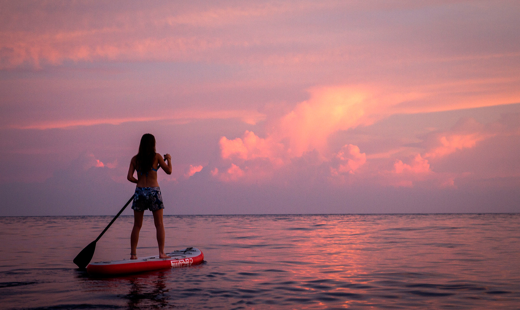 girl in summer shorts paddling SUP in ocean during sunset