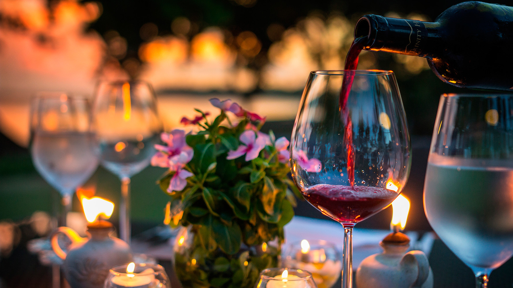 red wine poured into wine glass on a dinner table