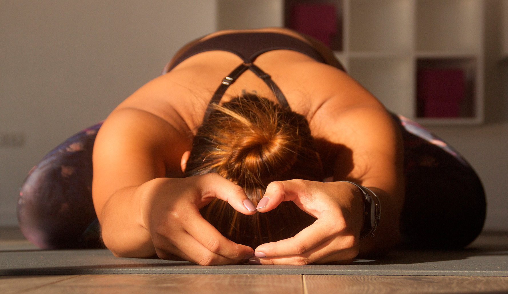 girl in yoga clothes doing a seated forward bend pose